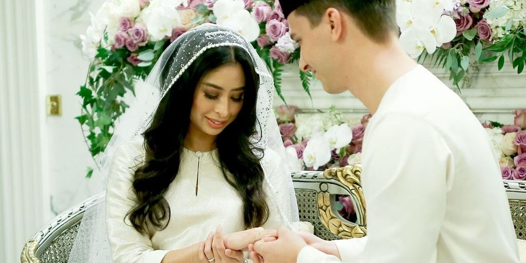 Attribution: [Image description: A bride and groom dressed in white are exchanging rings at an altar. The bride has long black hair, is wearing a veil, and is looking down happily at her hand. Behind them are beautiful flowers.] Via honey.nine.com.au
