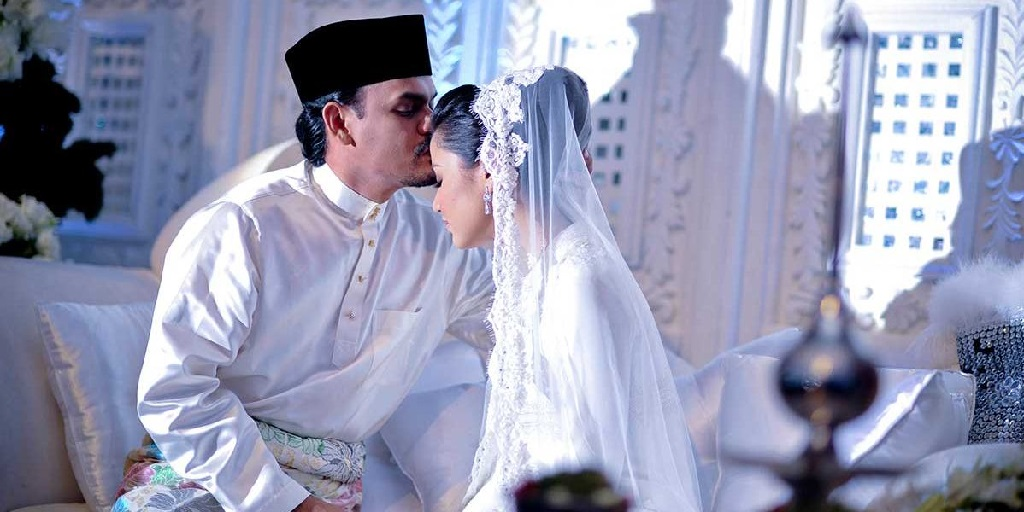 Attribution: [Image description: A bride and groom dressed in white are sitting together on their wedding day. The groom is kissing the bride on the forehead.] Via intrend.com.my