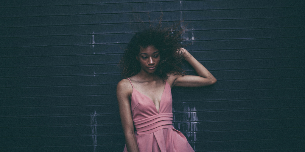 A black woman wears a pink dress.