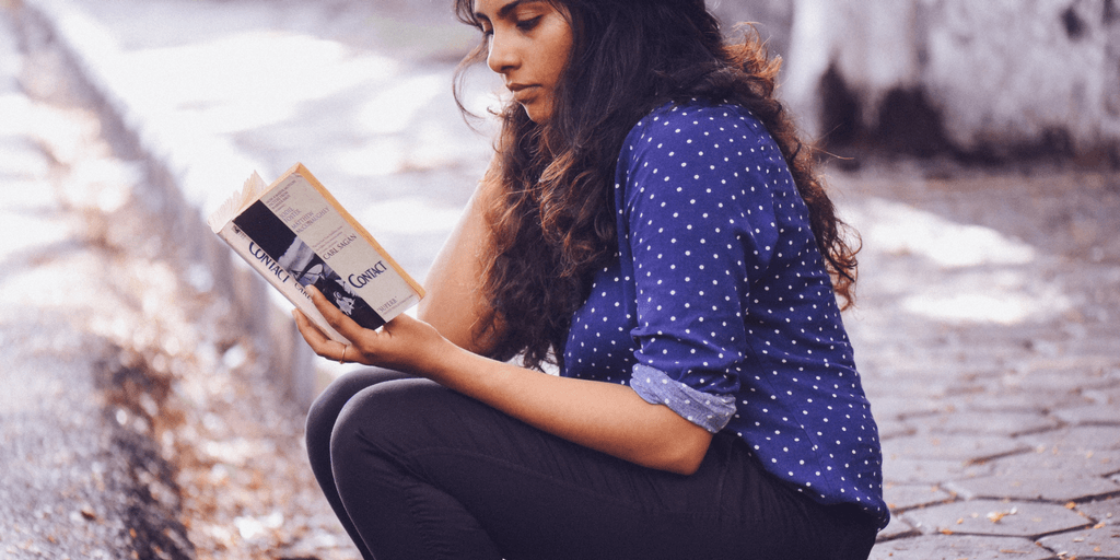[Image description: A woman sitting on a curb reading a book. She has long, curly, black hair, and is wearing a blue shirt with the sleeves rolled up. Image source: unsplash.com]