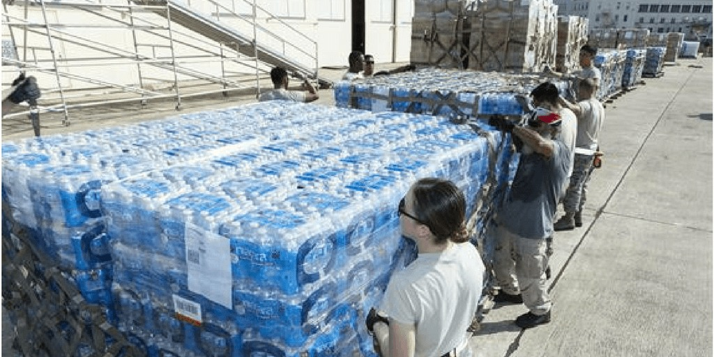 [image description: soldiers moving large cases of water] Via dla.mil