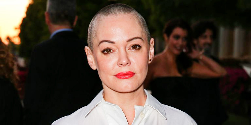 [Image description: Actress Rose McGowan staring into camera with shaved head and red lipstick.] Via Elle.com