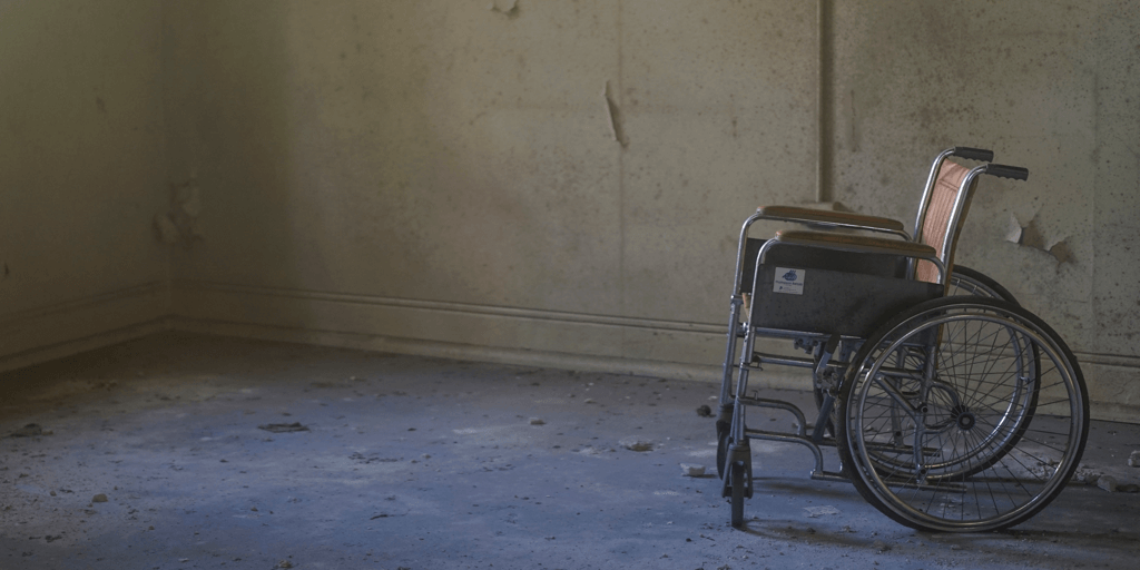 Image description: Empty wheelchair in what looks like an abandoned building room. Dirt and debris is on the floor. Source: Doug Maloney via Unsplash