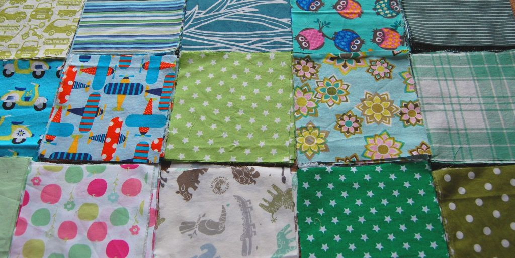 Patterned green and blue fabric is laid out in squares on a flat surface. It looks like it will be made into a quilt.