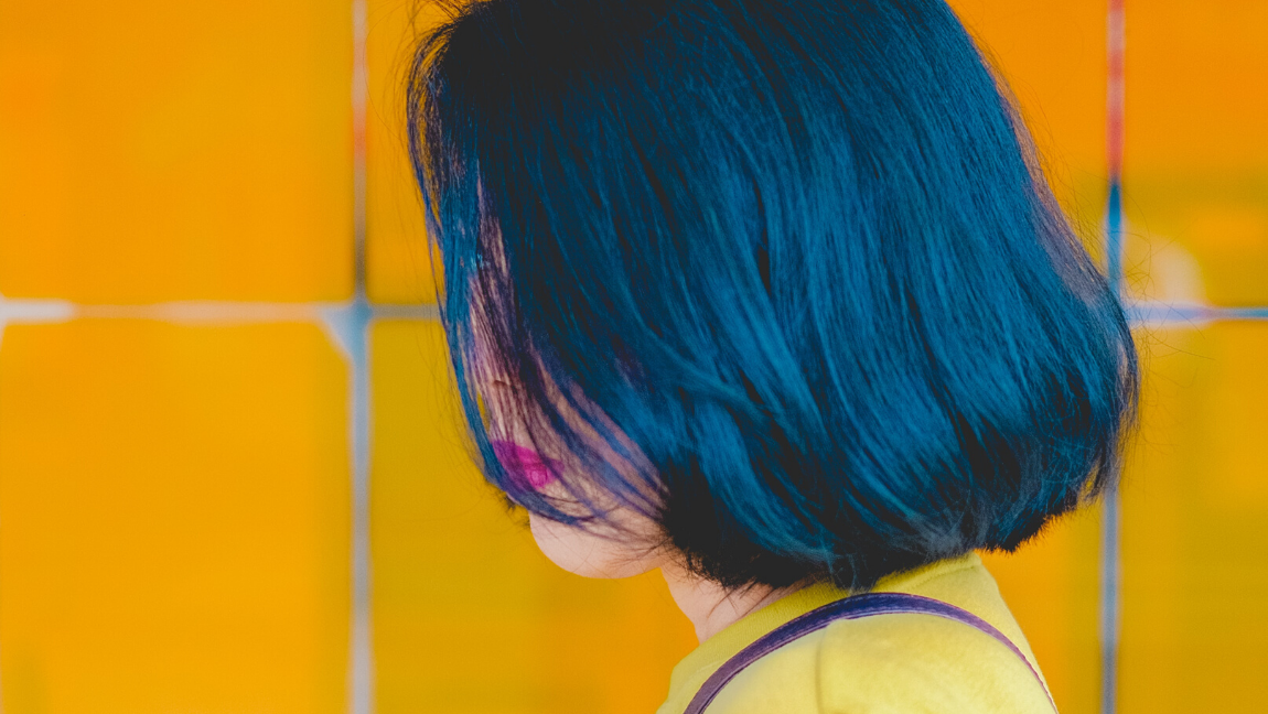 [Image description: Woman with short blue hair looks down, a bright yellow background behind her.] via Unsplash