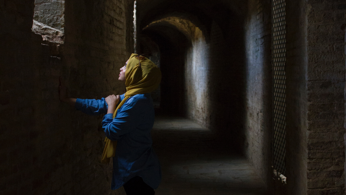 [Image Description: A woman wearing the hijab stares up into the light in a dark tunnel.] via Unsplash