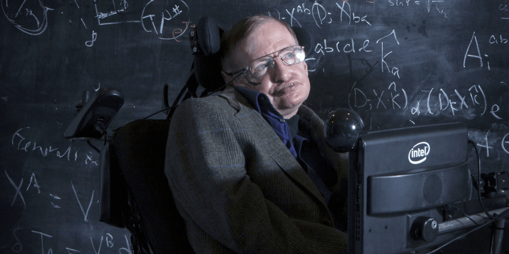 Stephen Hawking sits in front of a blackboard with mathematical equations written all over it.