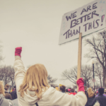 """a blonde woman carrying a sign that reads """"we are better than this"""" in the middle of a protest. She has her hand in a fist in the air."""