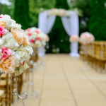 [Image description: Flowers on stands arranged to create an aisle leading to a makeshift altar that is draped in white. Rows of gold-colored chairs on are on both sides.] Via Unsplash.com