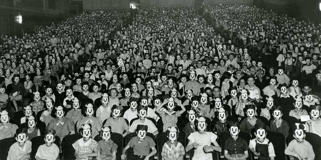 [Image Description: A black and white snapshot of a large crowd of individuals wearing white masks.] via medium.com