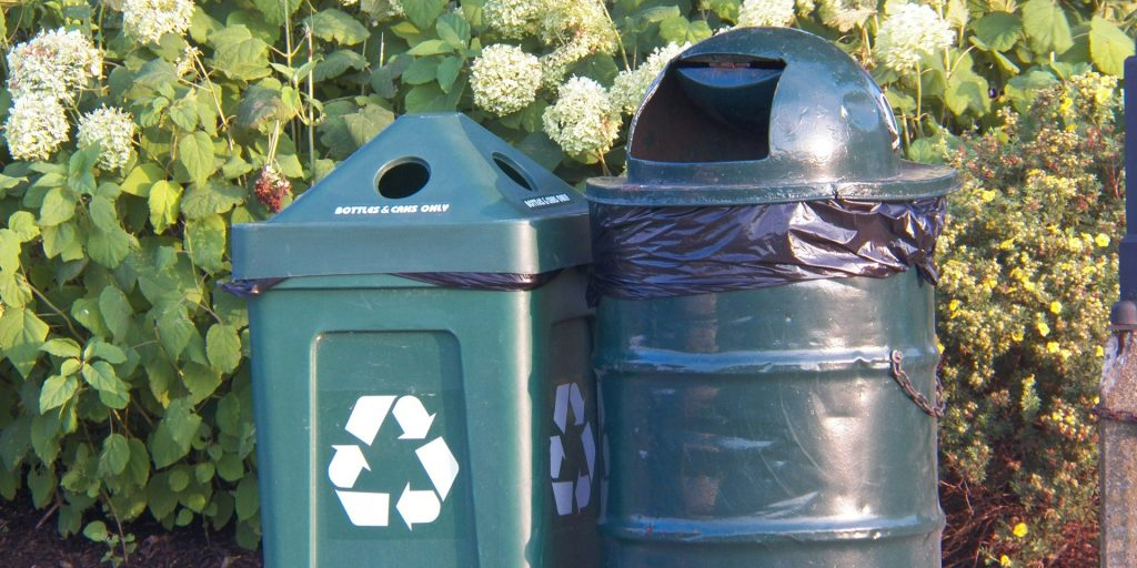 Two bins, one with a recycling symbol on it, stand outside.