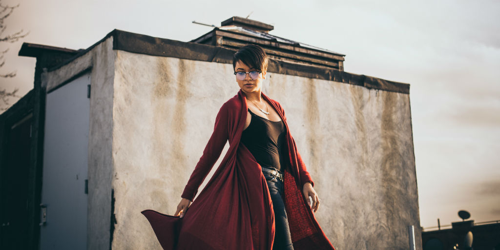 A short haired woman in glasses stands on a rooftop, she is gazing down as her long red cardigan floats around her.