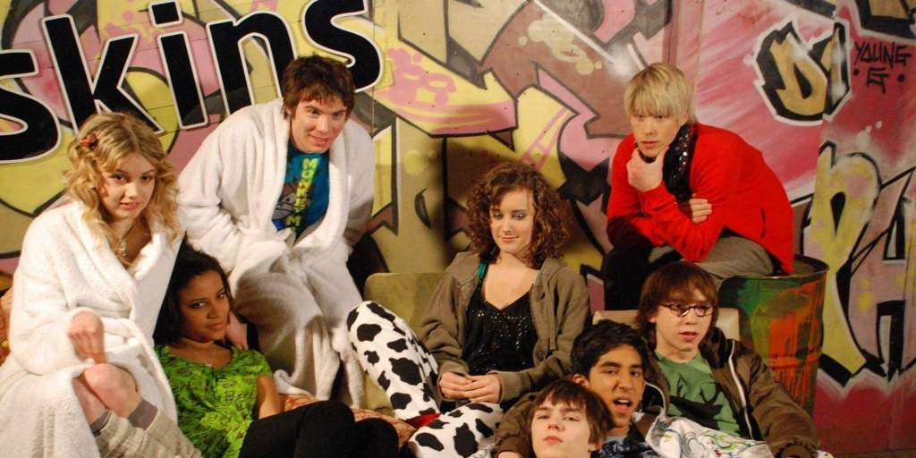 The cast of Skins seasons 1 and 2 sit around a couch. In the background, there is graffiti and the word 'Skins'.