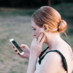 A red-headed woman in a sleeveless top is standing outside, scrolling through her phone.