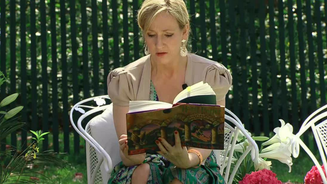 [Image Description: J.K. Rowling reading a Harry Potter book] Via Wikimedia Commons