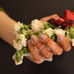 [Image Description: A left hand, with henna designs on the fingers and painted a nude pink, holding onto a bunch of flowers.]