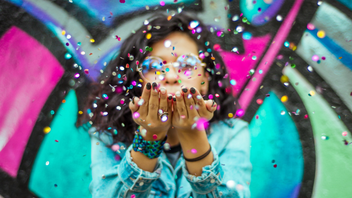 A woman is blowing on some colorful confetti.