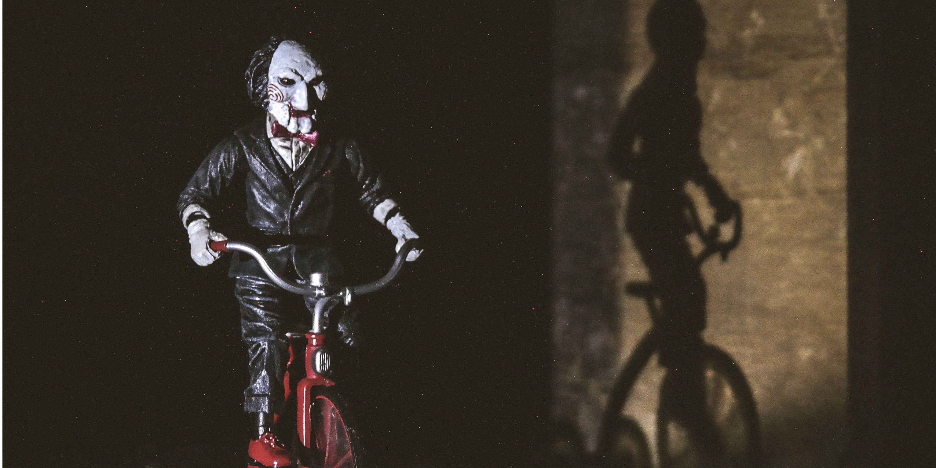 An image of Jigsaw, from the horror movie 'Saw'. Jigsaw is a scary puppet on a tricycle.