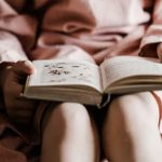 A picture of a girl with a book in her lap.