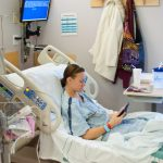 Image description: A woman sits in a hospital bed, reading her phone