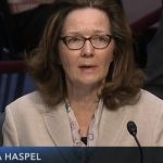A woman in front of a microphone answers questions at a Senate hearing.