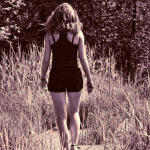 Image description: A black and white photo of a woman walking through a field. She is wearing workout clothes. / Via Pixabay