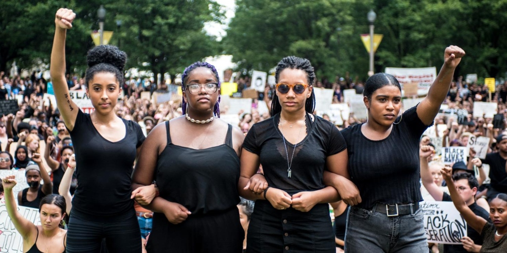 (From left to right) Sophia Byrd, Eva Lewis, Natalie Braye, and Maxine Wint led the sit-in rally at Millennium Park. (Colin Boyle)