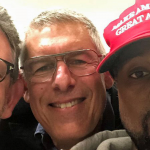 A photograph that was tweeted by Kanye West. It's a selfie of Kanye West wearing a red 'Make America Great Again' cap. He is standing next to two men, Lyor Cohen and Lucian Grainge, also Trump supporters.