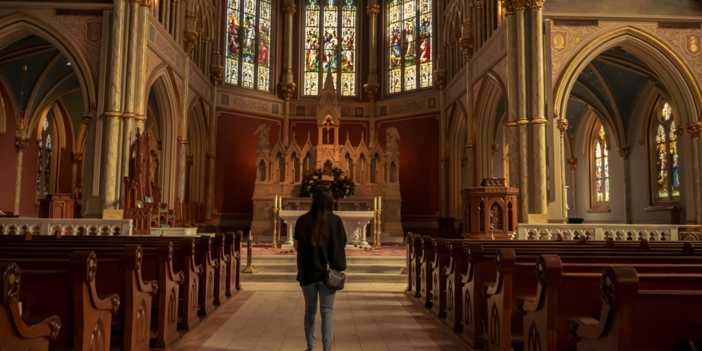 A girl stands in front of a church altar.
