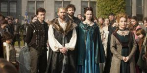 Anna Walton as Diane stands beside the King of France in a blue gown while Queen Catherine (Megan Follows) stands away, at a gathering on Reign