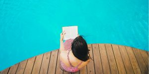Girl reading a book by a pool via Pixabay