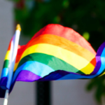 [Image description: A rainbow flag waves in the wind.] via Flickr