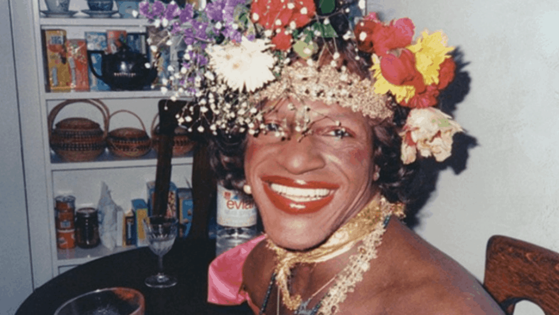 [Image description: Marsha P. Johnson wears a flower crown and smiles into the camera.] via The Marsha P. Johnson Institute