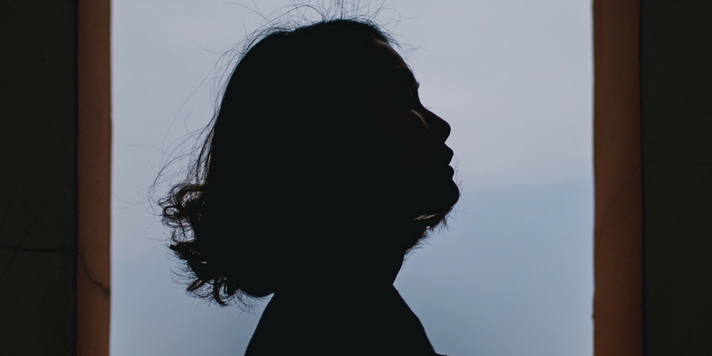 Image description: the silhouette of a woman with short hair.