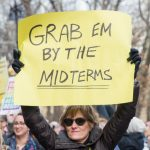 """Image description: a woman holds up the holds up a yellow poster sign that says """"Grab 'em by the midterms."""""""