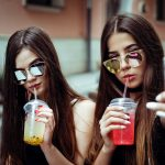 Image description: Two young women in sunglasses take a selfie on their phone while they drink colorful drinks through plastic straws.