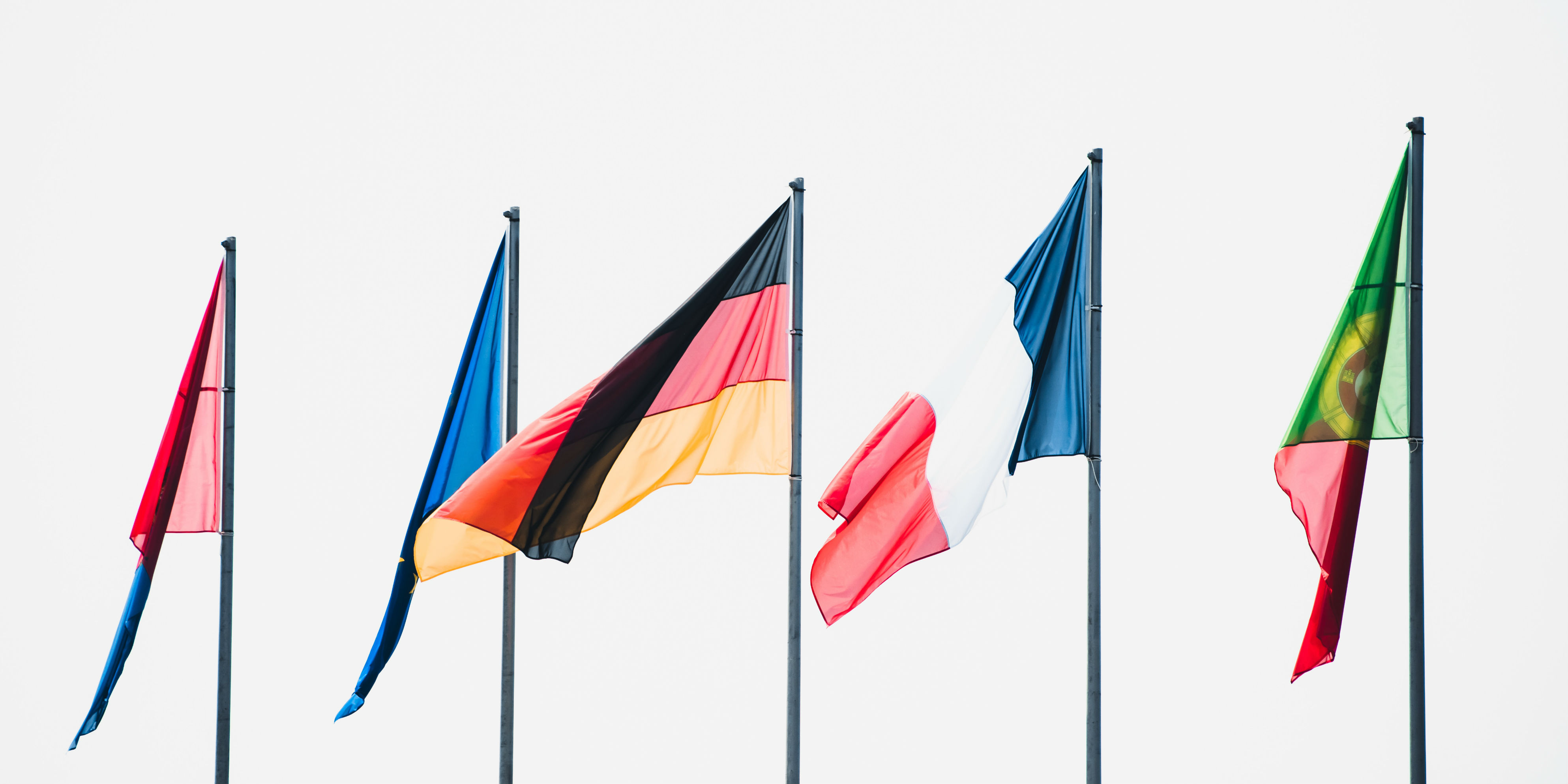 Flagpoles lined up, the German and French flags are visible and slightly waving in the wind