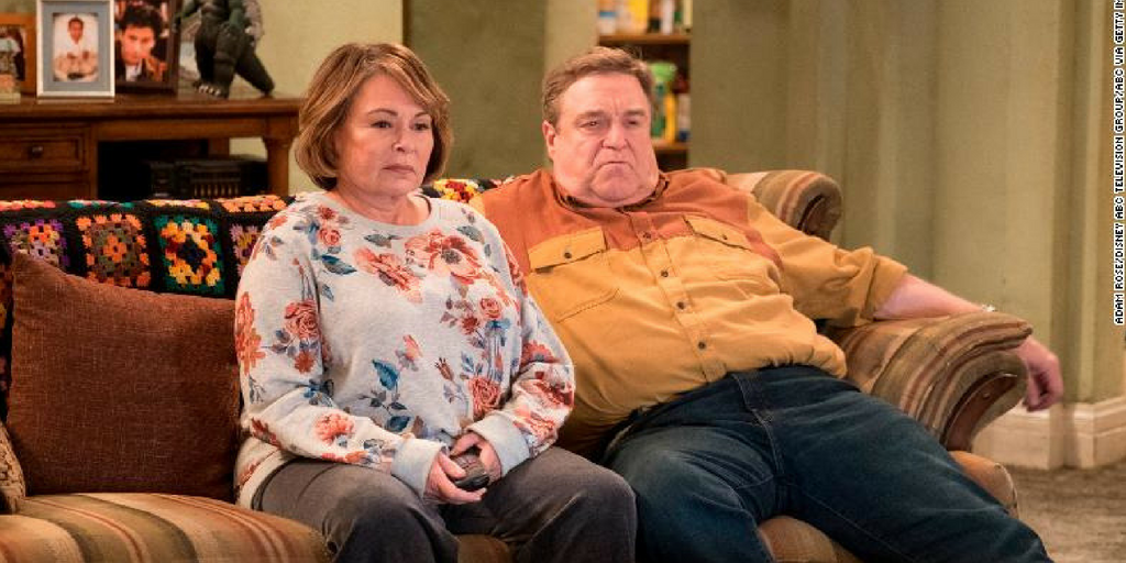 Roseanne and Dan sit on a couch.