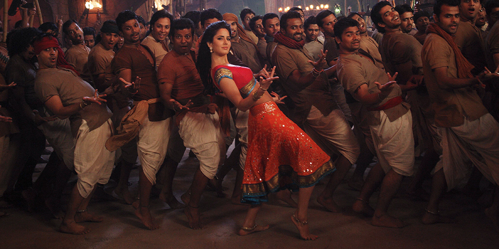[Image description: The actress Katrina Kaif caught mid-dance pose, surrounded by a roomful of men in the same pose.]