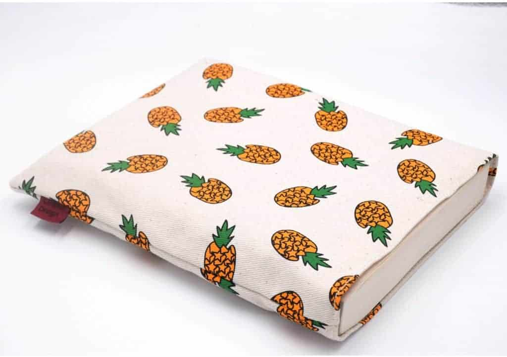 A white book sleeve atop a white background. The sleeve is peppered with cartoon pineapples.