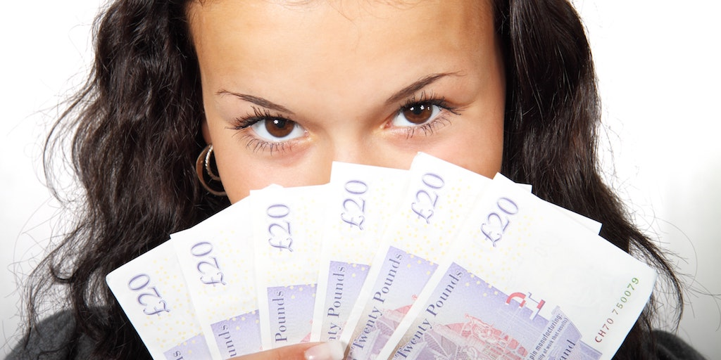 Via Pexels.com [Image description: A woman looks at the camera and covers the bottom of her face with a fanned out bunch of twenty pound notes.]