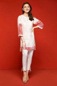 Model wearing a red and white embroidered tunic