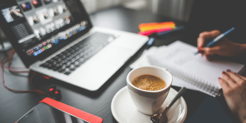 [Image description: A laptop is kept on the table along with a notepad and a pen in the hand of a person whose face isn't visible. A cup of coffee is also on the table.] Via Pexels