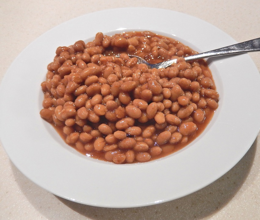 A white bowl of brown baked beans with a silver spoon.