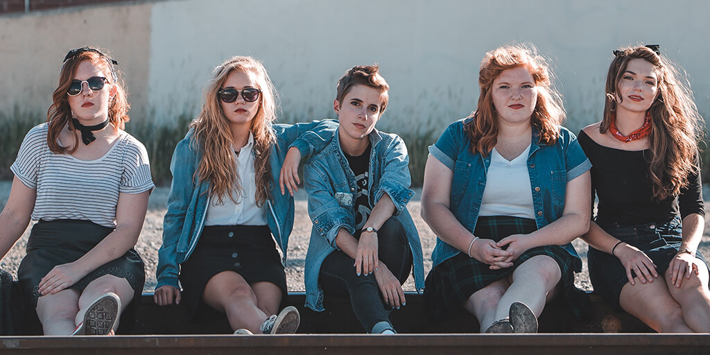 Five young women pose together on an empty railroad track on a sunny day.