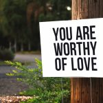 """A white signpost with the text 'You are worthy of love"""". There's greenery and a road in the background."""