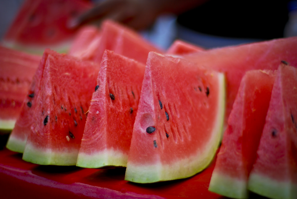 Sliced watermelon on a tray with black seeds.