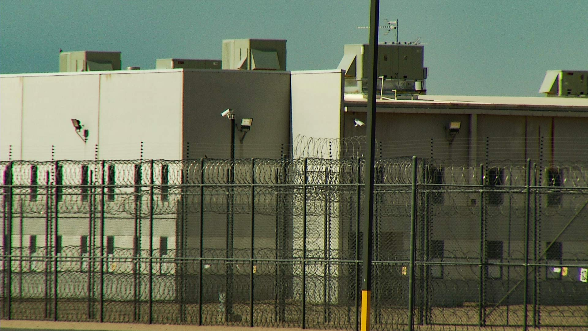 [Image description: The outside of a sand-colored, windowless building surrounded by high fences and barbed wire.]