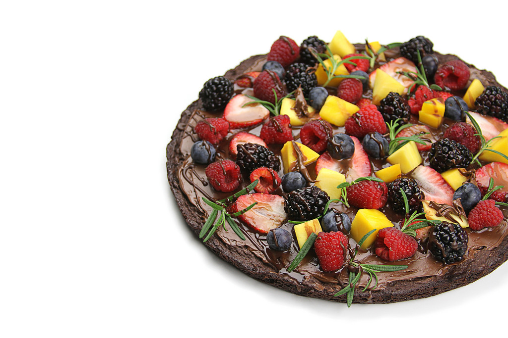 """A round brownie """"pizza"""" covered in fruit toppings including strawberries,  blueberries, raspberries, and mango chunks."""