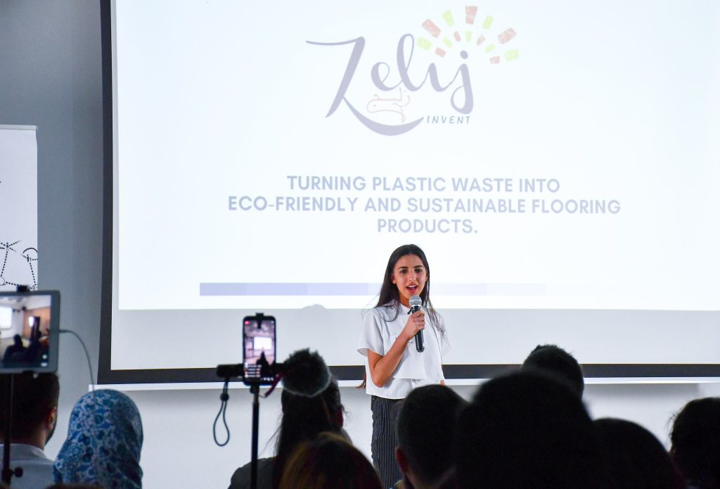 mage courtesy of Womena. Image description: The founder of Zelij, a woman in a white shirt and long dark hair speaks into a microphone in front of a crowd with the logo of her company behind her.